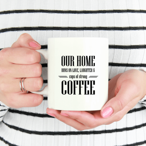 """Kaffekrus med teksten """"Our home runs on love, laughter and cups of strong coffee"""""""